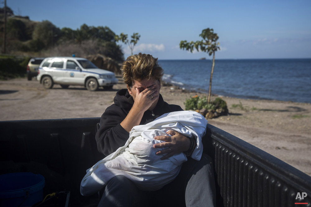 A local resident cries as she holds the body of a dead baby in Petra village on the northeastern Greek island of Lesbos, Friday, Oct. 30, 2015. The deaths occurred amid a surge of crossings to Greek islands involving migrants and refugees from Syria, Afghanistan and other countries ahead of winter and as European governments weight taking tougher measures to try and limit the number of arrivals in Europe. (AP Photo/Santi Palacios)
