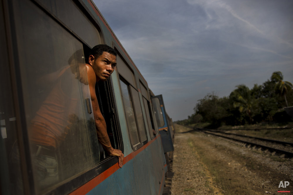 In this March 23, 2015 photo, a train passenger looks out at the countryside between Ciego de Avila and Santa Clara, Cuba. While the island is slowly modernizing its rail system, it remains the slowest way to get around already slow-moving Cuba. (AP Photo/Ramon Espinosa)