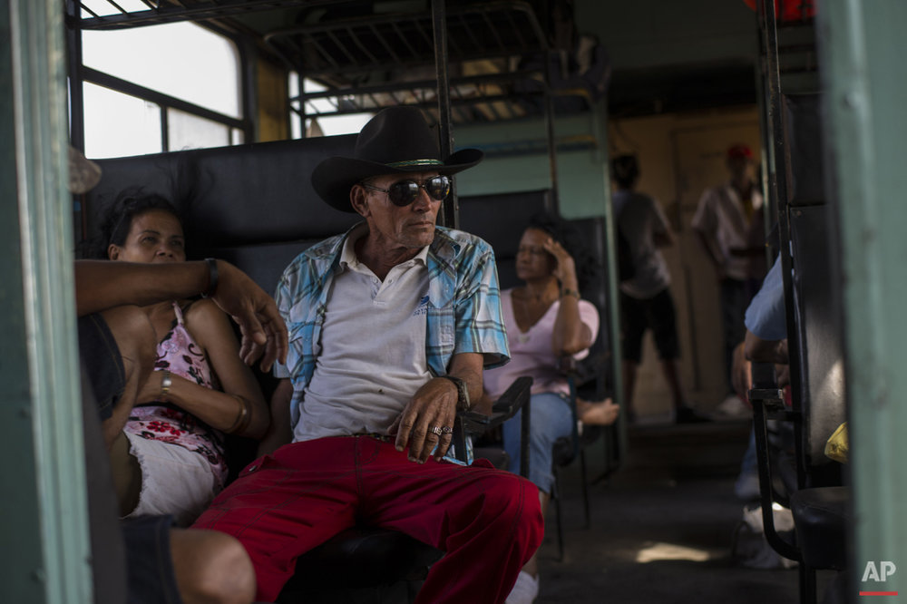 In this March 23, 2015 photo, a working cowboy travels by train to Santa Clara to participate in a rodeo, as the train moves through the province of Holguin, Cuba. From east to the west, trains offer a fine-grained, slow-moving view of Cuba that few foreigners ever see. (AP Photo/Ramon Espinosa)