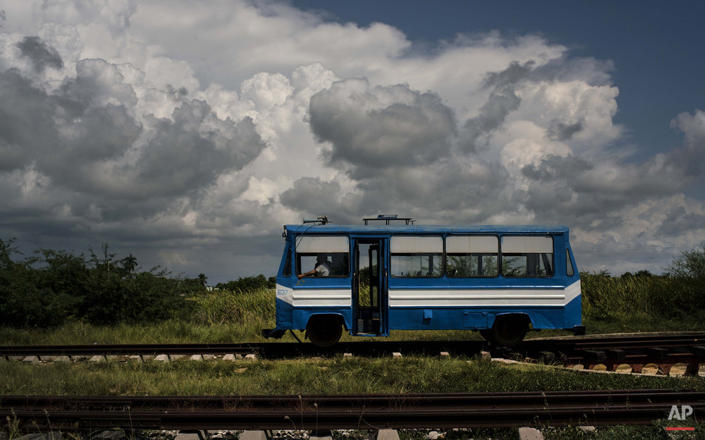 "In this Oct. 11, 2015 photo, a train wagon made to look like a bus, moves along the tracks on the outskirts of Trinidad, Cuba. This train, known as a ""train auto motor,"" moves passengers to and from the outskirts of the city. (AP Photo/Ramon Espinosa)"