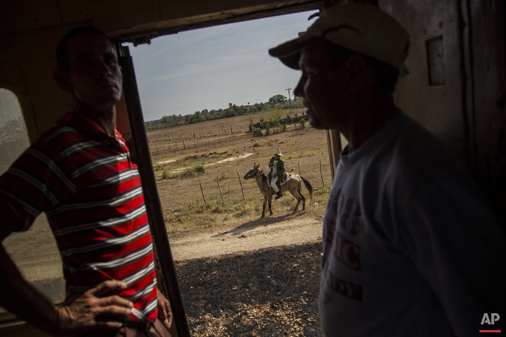 In this March 23, 2015 photo, passengers pass the time chatting on the landing of a train car as a farmer rides his horse alongside the tracks in the province of Holguin in Cuba. Cuba became the first Latin American country with a train system in the mid-19th century when colonial Spain began connecting Havana with the sugar-growing regions outside the capital. (AP Photo/Ramon Espinosa)