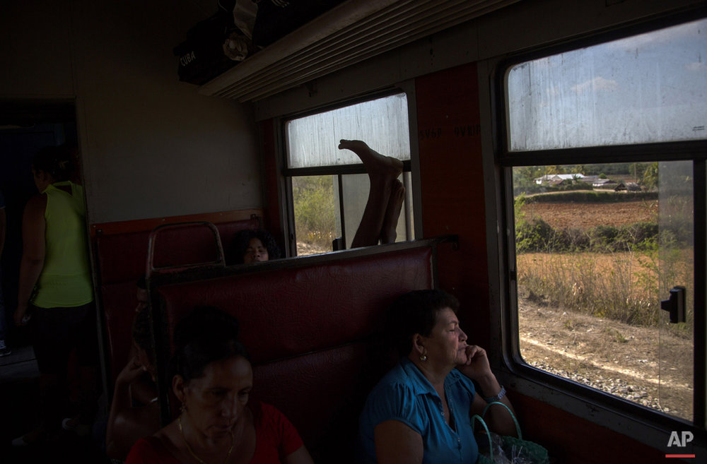 In this March 23, 2015 photo, a commuter puts his feet up in a train traveling from Santiago de Cuba to Santa Clara, in the province of Holguin, Cuba. The trip from Havana to Santiago, 475 miles (765 kilometers) to the east, takes an average of 15 hours, if the train doesn't break down. A slightly more reliable train with air conditioning currently is not running while it undergoes repairs. (AP Photo/Ramon Espinosa)
