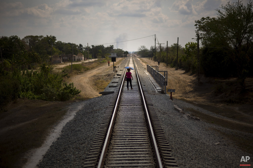 In this March 23, 2015 photo, a woman who just got off the train uses the tracks to cross a bridge after arriving to her destination in the province of Holguin, Cuba. Cuba became the first Latin American country with a train system in the mid-19th century, with the network growing to 5,600 miles of rails crisscrossing the island before the system fell into disrepair. Currently, a longstanding U.S. trade embargo makes it hard to get parts. (AP Photo/Ramon Espinosa)