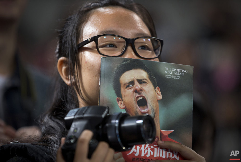 A woman watches Novak Djokovic of Serbia plays at a charity promotion activity event for the China Open tennis tournament at the National Tennis Stadium in Beijing, Saturday, Oct. 3, 2015 (AP Photo/Andy Wong)