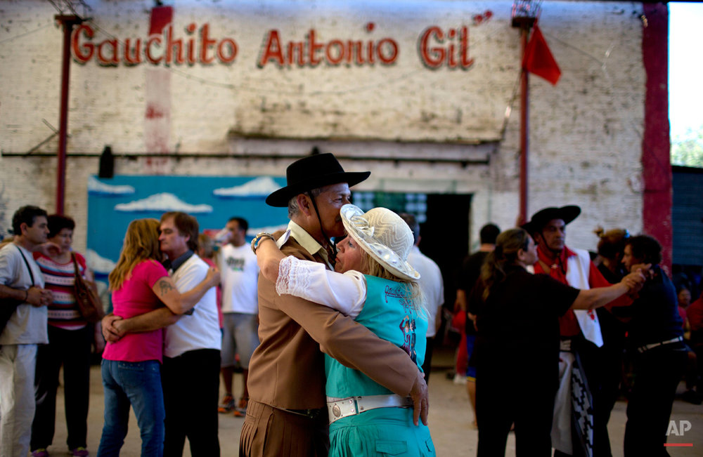 In this Nov. 8, 2014 photo, people dressed as South American cowboys dance at a sanctuary built in honor of Gauchito Gil on the anniversary of his death in Alejandro Korn, Argentina. On every 8th of the month, followers of Gil pay tribute to him, leaving offerings at roadside altars and ask for him to answer their prayers. (AP Photo/Natacha Pisarenko)