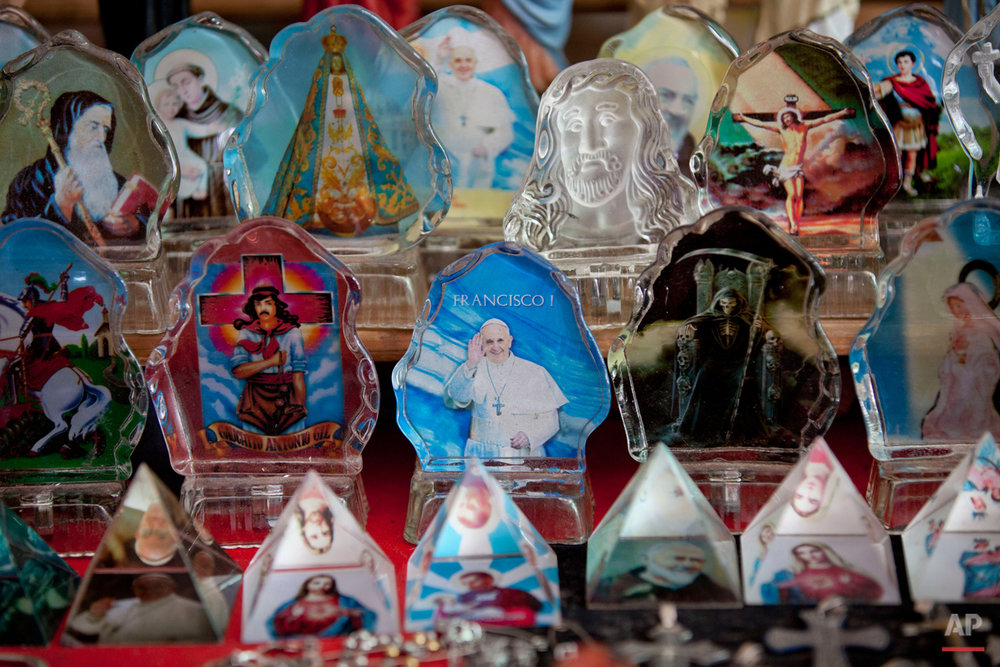 In this Oct. 30, 2014 photo, a figure of Pope Francis, center, Gauchito Gil, left, and San La Muerte, right, sit for sale among other religious figures in a slum in Buenos Aires, Argentina. Gauchito Gil and San La Muerte are just two of many folk saints, not recognized by the Roman Catholic Church, which are flourishing in Argentina, the homeland of Pope Francis. The phenomenon is not new, but experts say it surged after the South American countryís 2001 financial crisis which caused poverty rates to soar and people to seek out popular religiosity.  (AP Photo/Natacha Pisarenko)
