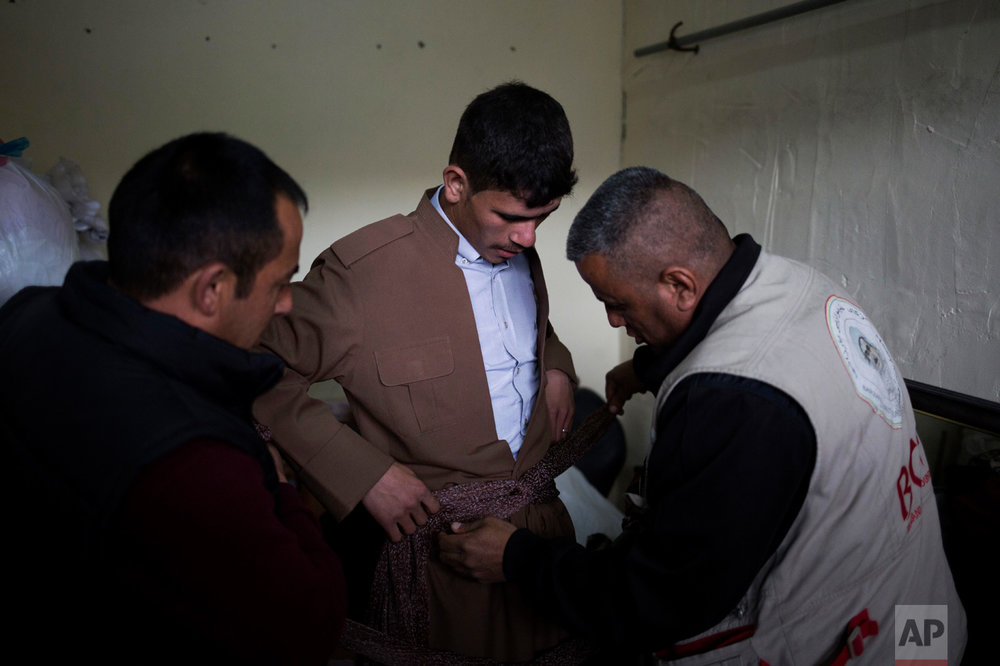 Hussein Zeino Danoon, 25, gets dressed in Kurdish traditional clothing for his wedding on Thursday, Feb. 16, 2017. He married 16-year-old Shahad Ahmed Abed in the Khazer camp for displaced people from Mosul. (AP Photo/Bram Janssen)