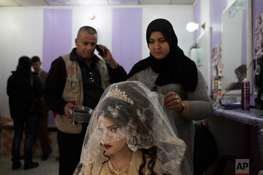 Shahad Ahmed Abed, 16, gets her hair done in a hair salon in Khazer for the wedding on Thursday, Feb. 16, 2017. Abed and her husband Hussein Zeino Danoon both fled from Mosul within the last month, just as Iraqi forces pushed Islamic State militants out of the eastern side of the city. (AP Photo/Bram Janssen)