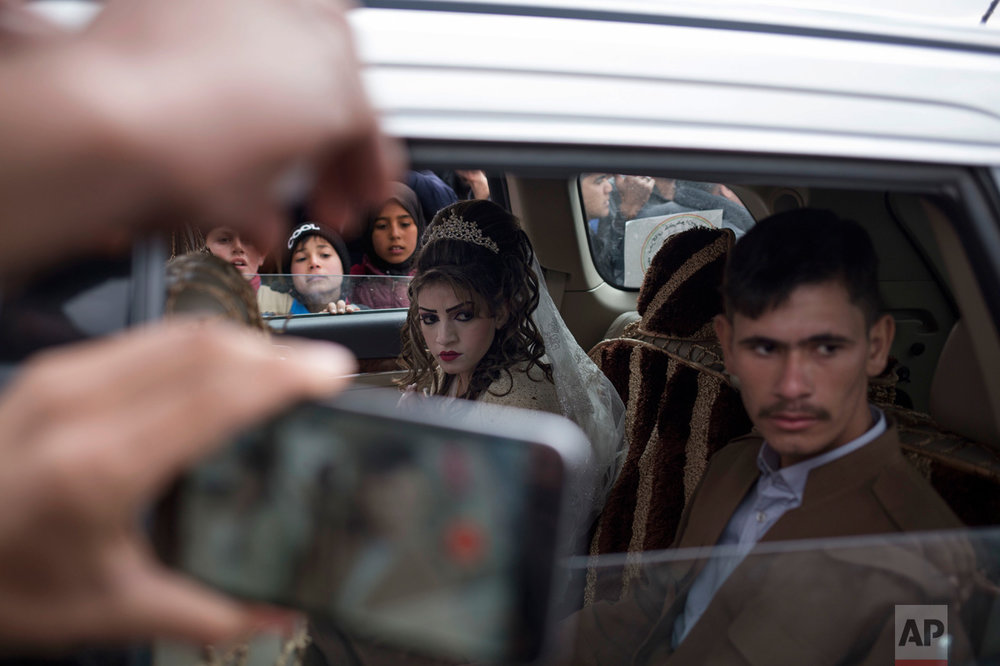 Hussein Zeino Danoon and Shahad Ahmed Abed sit inside the car after marrying in the Khazer camp for displaced people from Mosul, Thursday, Feb. 16, 2017. It's the second marriage to take place in the IDP camps east of the city where tens of thousands are living, having fled the fighting in Mosul. (AP Photo/Bram Janssen)