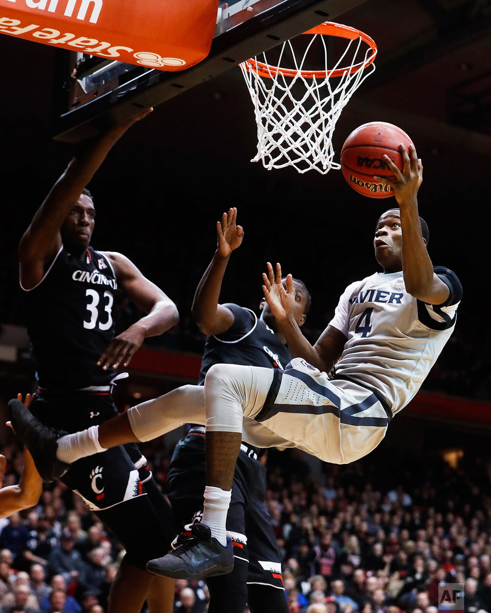 Xavier's Edmond Sumner (4) shoots against Cincinnati's Nysier Brooks (33) during the second half of an NCAA college basketball game, Thursday, Jan. 26, 2017, in Cincinnati. (AP Photo/John Minchillo)