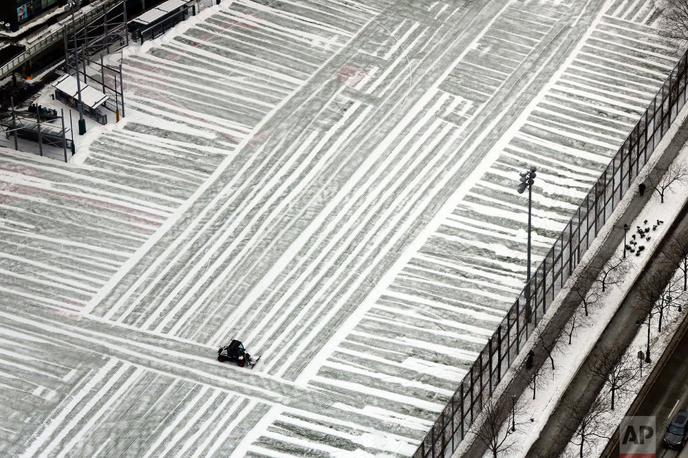 A lone plow clears a playground in lower Manhattan, photographed from New York's One World Trade Center building, Monday, Jan. 9, 2017. As the East Coast waits to thaw out from a weekend icy mess, another storm is bringing rain and the potential of the worst flooding in more than a decade to the West coast. (AP Photo/Richard Drew)