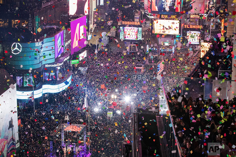 Revelers celebrate the new year as confetti flies over New York's Times Square as seen from the Marriott Marquis, Sunday, Jan. 1, 2017. (AP Photo/Mary Altaffer)