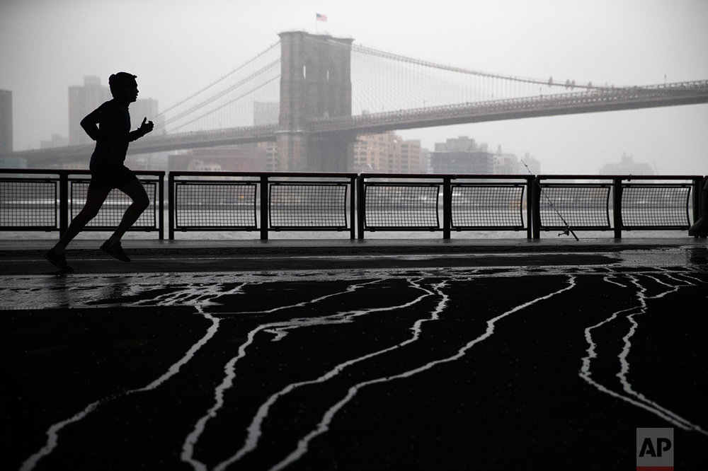 Snow falls as a jogger, framed by the Brooklyn Bridge, runs underneath the Franklin Delano Roosevelt Drive overpass, Tuesday, Jan. 31, 2017, in lower Manhattan. (AP Photo/Mary Altaffer)