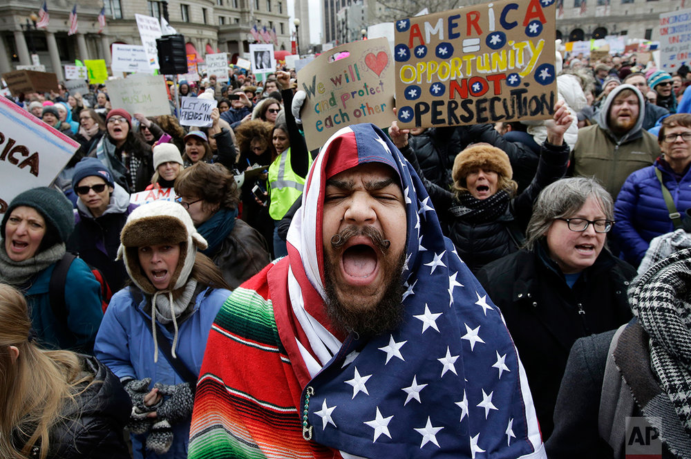 Izzy Berdan, of Boston, center, wears an American flags as he chants slogans with other demonstrators during a rally against President Donald Trump's order that restricts travel to the U.S., Sunday, Jan. 29, 2017, in Boston. Trump signed an executive order Friday, Jan. 27, 2017 that bans legal U.S. residents and visa-holders from seven Muslim-majority nations from entering the U.S. for 90 days and puts an indefinite hold on a program resettling Syrian refugees. (AP Photo/Steven Senne)