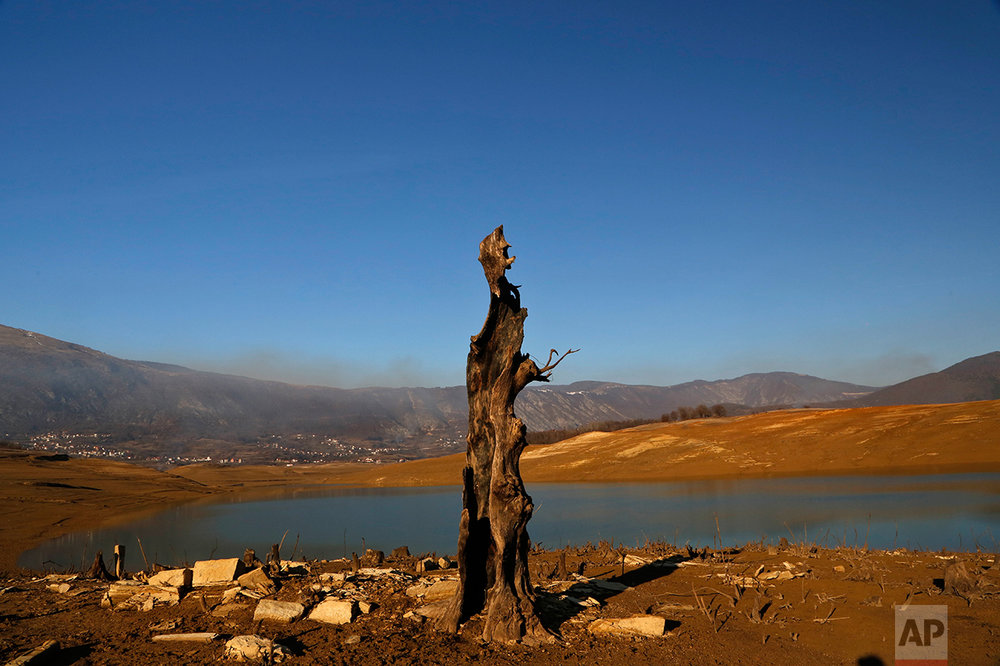 In this photo taken on Thursday, Feb. 16, 2017 the remains of a house lay at the bottom of the drained Ramsko Lake, near the Bosnian town of Rama, 130 kms south of Sarajevo. When artificial Ramsko Lake was filled nearly 50 years ago villages in what was at that time a fertile valley slipped from sight. Half a century later, the remains of their crumbled houses and cracked tombstones of their elders have been exposed as most of the lake had vanished following an exceptionally cold and dry winter. ( AP Photo/Amel Emric)