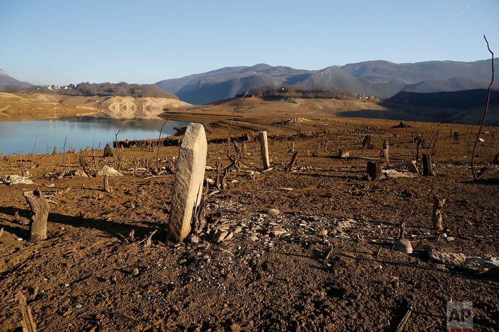 In this photo taken on Thursday, Feb. 16, 2017 remains of graves at the local cemetery lie at the bottom of the drained Ramsko Lake, near the Bosnian town of Rama, 130 kms south of Sarajevo. The artificial lake was made nearly 50 years ago, in what was at that time a fertile valley, and nearly 2,000 people had to forsake their ancestral homes. Half a century later, the remains of their crumbled houses and cracked tombstones of their elders have been exposed as most of the lake has vanished following an exceptionally cold and dry winter. ( AP Photo/Amel Emric)