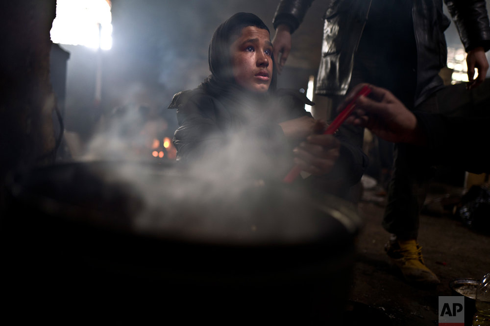 In this Saturday, Feb. 4, 2017 photo, unaccompanied minor Liaqat, 12, a migrant from Khogyani, Afghanistan, cooks on a fire in an abandoned warehouse where he and other migrants took refuge in Belgrade, Serbia. (AP Photo/Muhammed Muheisen)