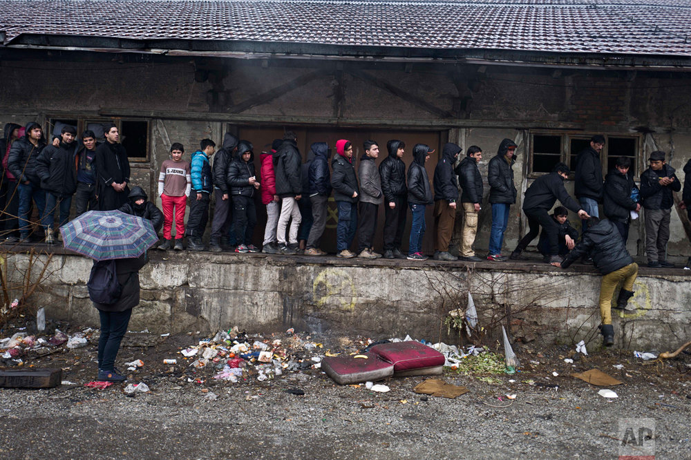 In this Saturday, Feb. 4, 2017 photo, unaccompanied minor, Ali, 12, a migrant from Jalalabad, Afghanistan, left wearing a red pants, queue for food outside an abandoned warehouse where he and other migrants took refuge in Belgrade, Serbia. (AP Photo/Muhammed Muheisen)