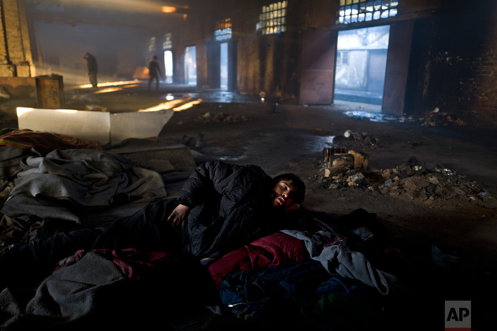In this Saturday, Feb. 4, 2017 photo, unaccompanied minor Obaidullah, 14, a migrant from Wardak, Afghanistan, sleeps on the ground of an abandoned warehouse where he and other migrants took refuge in Belgrade, Serbia. (AP Photo/Muhammed Muheisen)