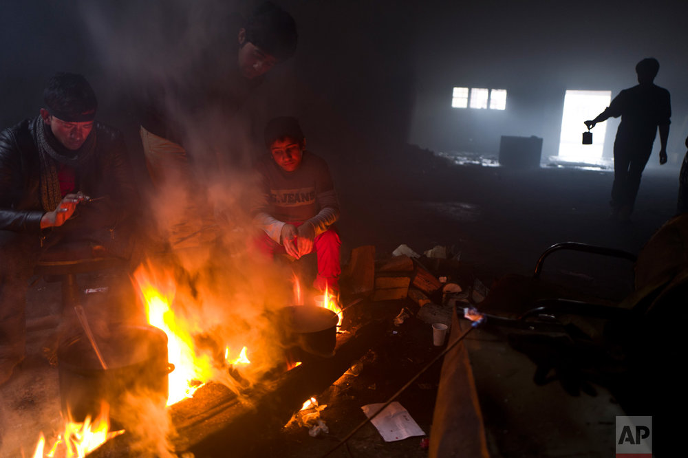 In this Saturday, Feb. 4, 2017 photo, unaccompanied minor, Ali, 12, a migrant from Jalalabad, Afghanistan, sits while cooking on a fire in an abandoned warehouse where he and other migrants took refuge in Belgrade, Serbia. (AP Photo/Muhammed Muheisen)
