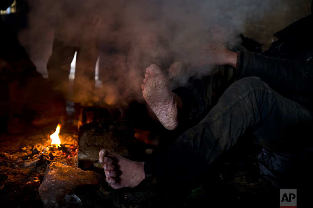 In this Wednesday, Feb. 8, 2017 photo, unaccompanied minor Matiuallah, 14, a hearing impaired and unable to speak migrant from Afghanistan, warms his feet by a fire shortly after arriving from the Bulgarian border to an abandoned warehouse in Belgrade, Serbia. (AP Photo/Muhammed Muheisen)