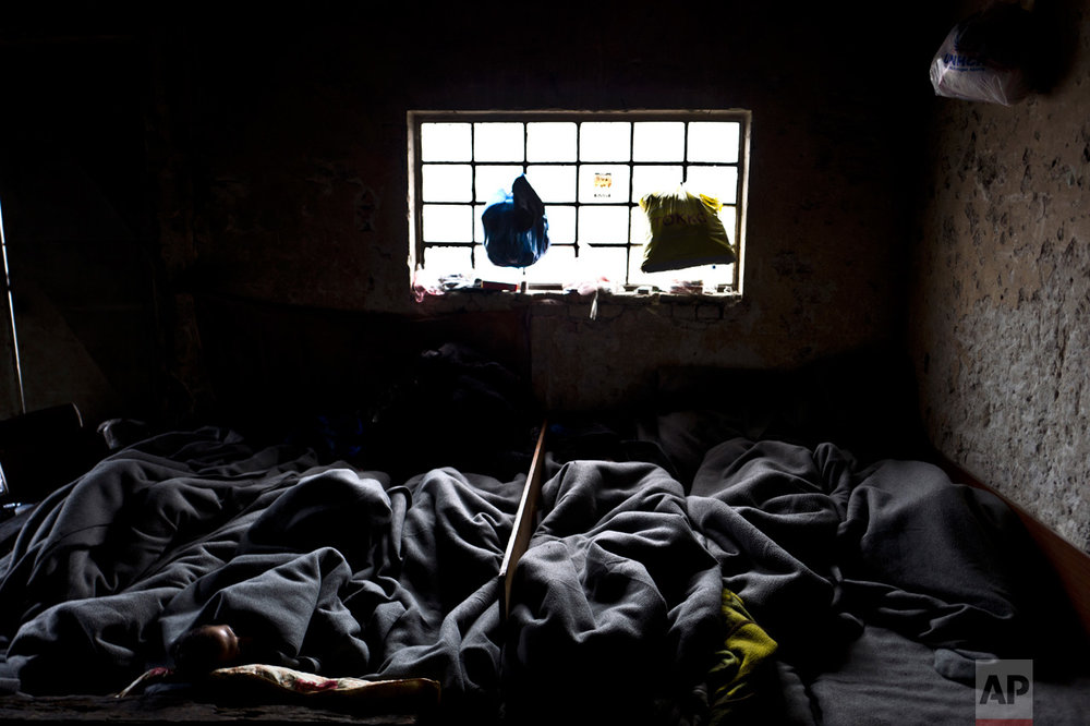 In this Tuesday, Feb. 7, 2017 photo, unaccompanied minors, right, sleep on the ground with older ones in an abandoned warehouse where they took refuge in Belgrade, Serbia. (AP Photo/Muhammed Muheisen)