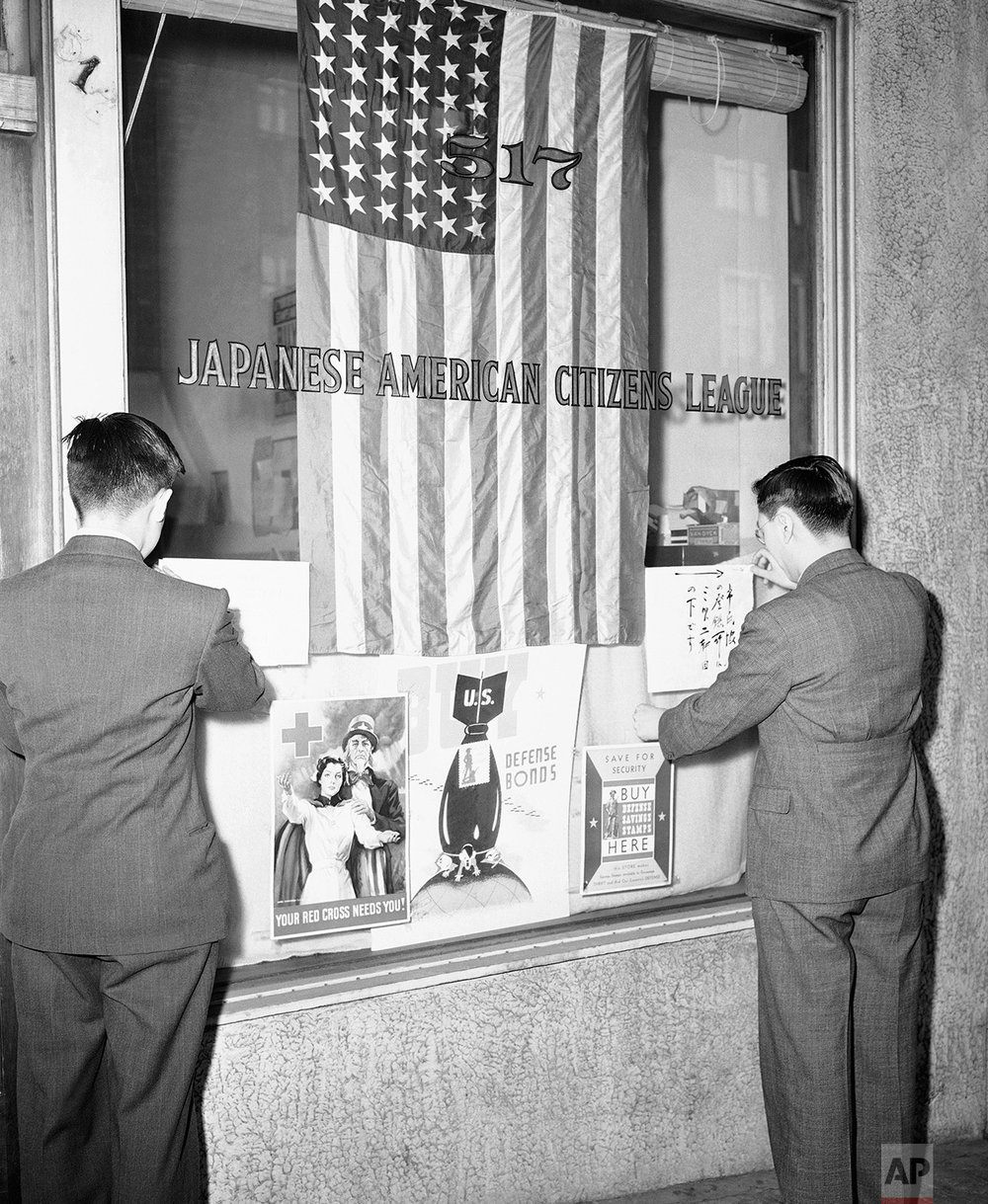 Officials of the Seattle Japanese - American Citizens League post signs outside league office March 11, 1942 notifying Seattle's Japanese population that all must register for themselves and their families. This is to facilitate possible future evacuation orders. (AP Photo)