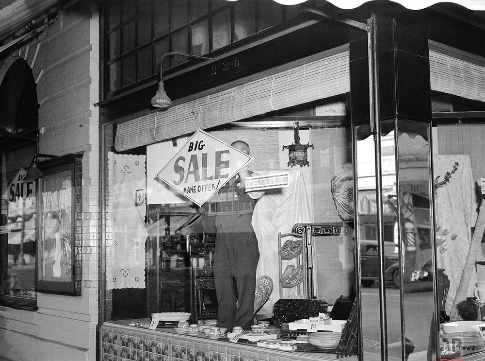 "Bargains, with articles marked down as much as 40 percent, were on everywhere in Los Angeles' ""Little Tokyo"", March 5, 1942, as its Japanese residents prepare to leave following the issuance of orders for the evacuation of enemy aliens and American-born Japanese from specified combat zones along the Pacific coast. T. Horiuchi, proprietor of one of the largest Asian art stores in the district, posts a sale sign in his window. Alongside is a sign declaring, ""We are 100 percent for the United States."" (AP Photo)"