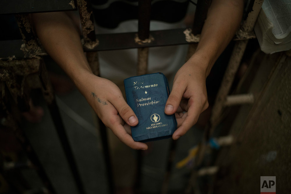 In this Feb. 6, 2017 photo, a detainee holds a Bible inside an overcrowded cell at a police station near Manaus, Brazil. A recent study by think-tank Fundacao Getulio Vargas estimates that 40 percent of Brazilian prisoners have not been convicted. (AP Photo/Felipe Dana)