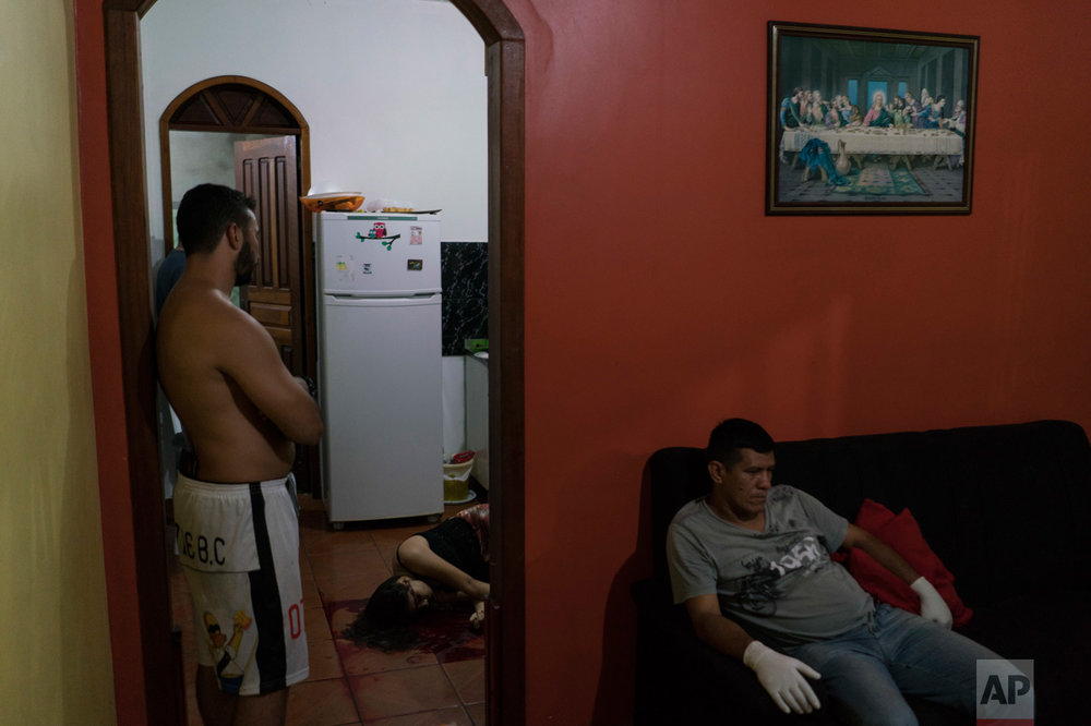 In this Feb. 5, 2017 photo, a gloved morgue worker rests at a home where the body of a woman lies on the kitchen floor after she was shot to death under unclear circumstances in Manaus, Brazil. The increasingly violent city is a thoroughfare for drug trafficking across South America, where authorities suspect most murders are gang related. (AP Photo/Felipe Dana)