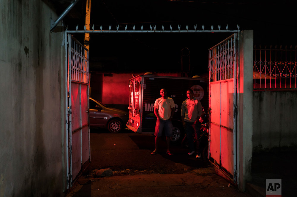 "In this Feb. 5, 2017 photo, residents watch police inspect a home where a woman was shot to death in Manaus, Brazil. ""Citizens are the ones who are truly jailed these days,"" said Claudio Lamachia, head of Brazil's bar association. ""Members of the crime gangs are dictating the rules and stopping people from leaving their homes."" (AP Photo/Felipe Dana)"
