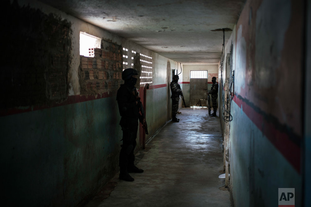 In this Feb. 2, 2017 photo, guards stand outside prison cells at the Monte Cristo agricultural penitentiary in Boa Vista, Brazil. Guards, administrative prison staff and families of inmates of this prison said gang leaders ordered newcomers to join killing sprees in January and dismember and behead the dead. (AP Photo/Felipe Dana)
