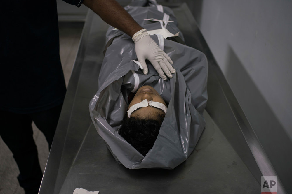 In this Feb. 4, 2017 photo, a morgue worker prepares the body of a homicide victim at a hospital in Manaus, Brazil. According to Claudio Lamachia, head of Brazil's bar association, Brazil's prisons are universities of crime, and from the inside, leaders give orders to commit crimes on the outside, including murder. (AP Photo/Felipe Dana)