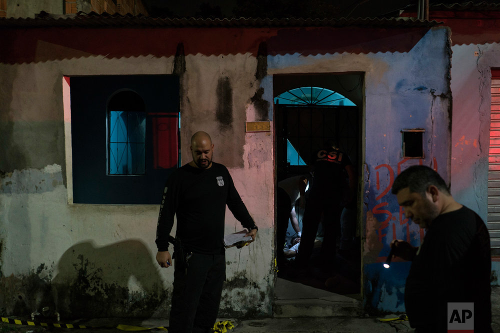 In this Feb. 5, 2017 photo, police inspect a home where a murder victim lies on the floor in Manaus, Brazil. The increasingly violent city is a thoroughfare for drug trafficking across South America, where authorities suspect most murders are gang related. (AP Photo/Felipe Dana)