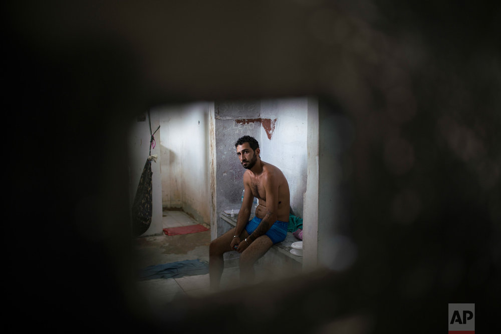 In this Feb. 2, 2017 photo, an inmate sits inside a cell separated from the main prison population, at the Monte Cristo agricultural penitentiary in Boa Vista, Brazil. Many inmates shouted that they need medical attention. (AP Photo/Felipe Dana)