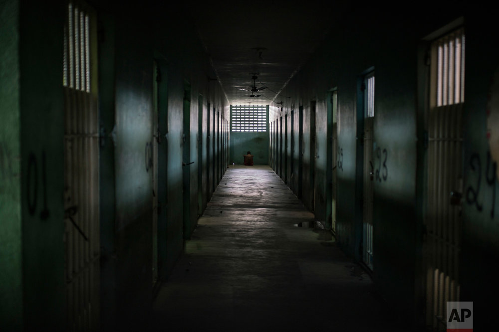 In this Feb. 2, 2017 photo, an inmate sits facing the wall at the end of a corridor between cells at the Monte Cristo agricultural penitentiary in Boa Vista, Brazil. Some prisoners serving time for lesser crimes were forced to participate in gang-driven slaughters that left at least 130 inmates dead in January. (AP Photo/Felipe Dana)
