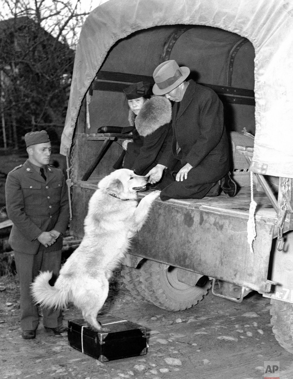 This Bainbridge Island Japanese man and wife give a farewell pat to their dog in Seattle, Washington, March 31, 1942 as they leave their island home for California internment camp. Army orders prohibited Japanese being interred from taking anything but personnel clothing, silverware, etc. Other belongings are being kept stored for the duration in a large warehouse under 24-hour armed guard. (AP Photo)
