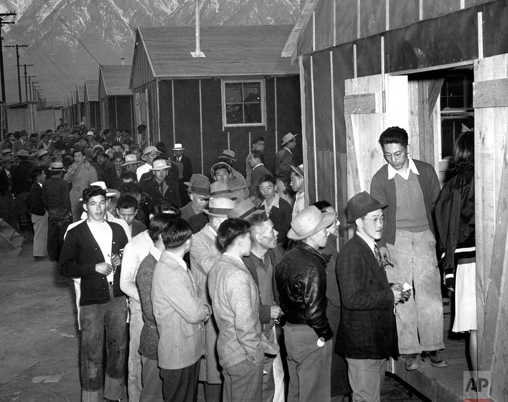Japanese citizens wait in line for their assigned homes at an internment camp reception center in Manzanar, Calif., on March 24, 1942. Many were forced from their homes in Los Angeles by the U.S. Army. (AP Photo)