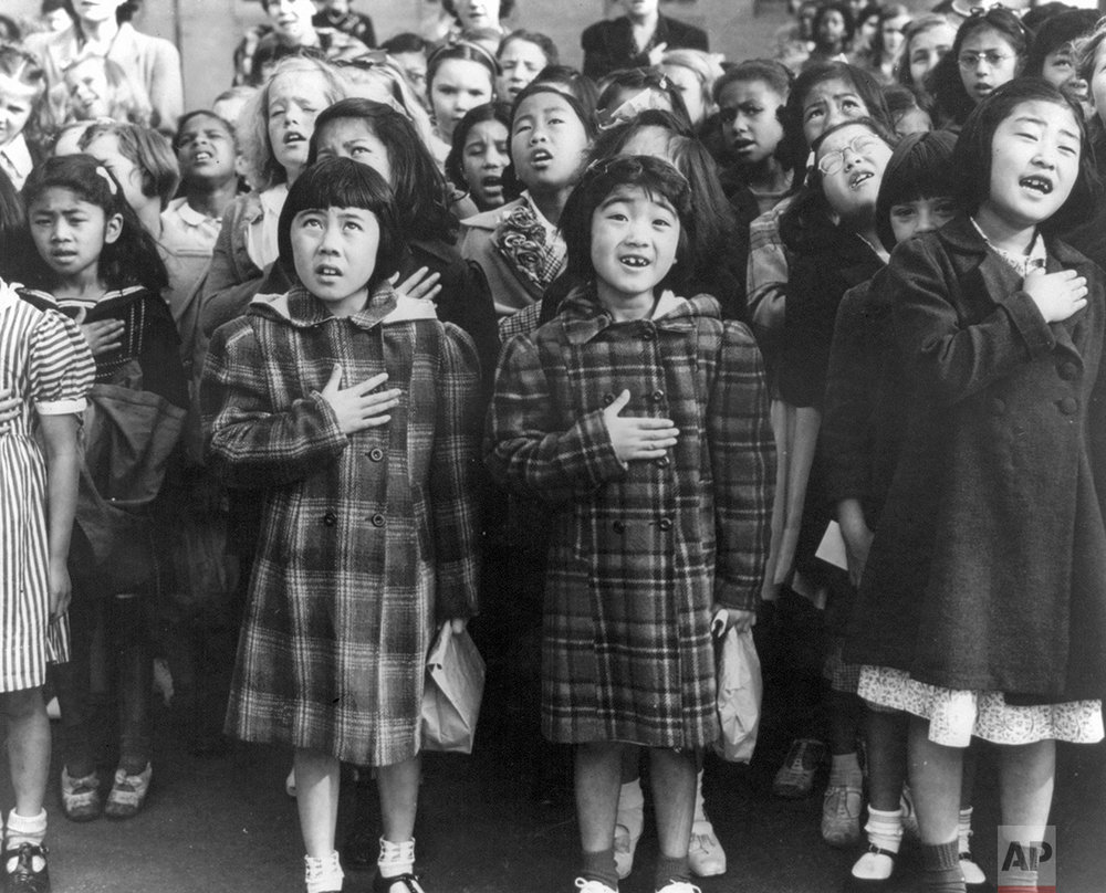 In this April 1942 photo made available by the Library of Congress, children at the Weill public school in San Francisco recite the Pledge of Allegiance. Some of them are evacuees of Japanese ancestry who will be housed in War Relocation Authority centers for the duration of the war. Roughly 120,000 Japanese immigrants and Japanese-Americans were sent to camps that dotted the West because the government claimed they might plot against the U.S. (Dorothea Lange/U.S. War Relocation Authority via AP)