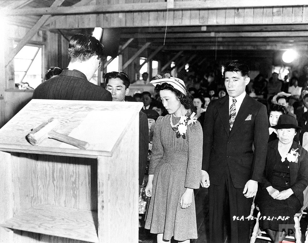 The first wedding at the assembly center. Pete Miyashito is being married to Toya Matashito, with the Reverend Donald T. Toriumi of the Presbyterian Church officiating in Santa Anita, California  July 2, 1942. There are 20 Protestant Ministers and five Buddhist Priests interned at the center. (AP Photo)
