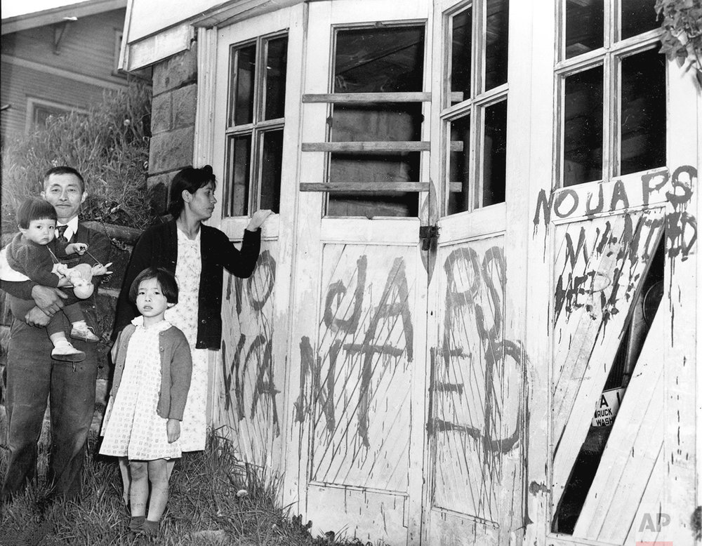 A Japanese family returns from a relocation center camp in Hunt, Idaho, to find their home and garage vandalized with anti-Japanese graffiti and broken windows in Seattle, Wa., May 10, 1945.  (AP Photo)