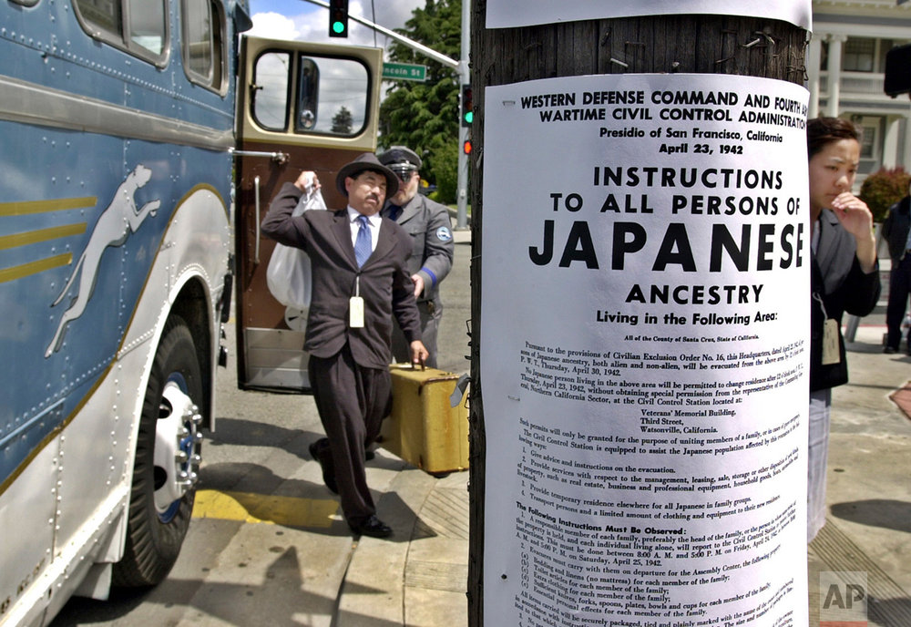In this April 27, 2002 photo, a copy of a poster from 1942 is posted in front of an antique Greyhound bus in downtown Watsonville, Calif., as participants reenact what happened to their relatives exactly 60 years earlier during their internment in 1942. Roughly 120,000 Japanese immigrants and Japanese-Americans were sent to desolate camps that dotted the West because the government claimed they might plot against the U.S. (AP Photo/Paul Sakuma)