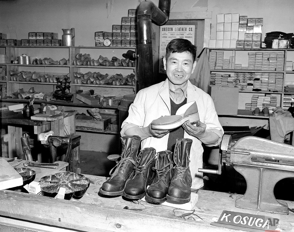 Mitsutaro Miyahara is in charge of the shoe shop at Tule Lake, Calif., Japanese relocation center.  Miyahara holds a pair of shoes he made of wood and he made the leather ones in the foreground, May 21, 1943. (AP Photo)