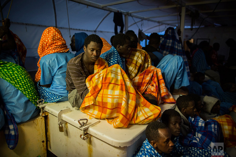 Refugees and migrants rest aboard the Golfo Azurro, the Spanish NGO Proactiva Open Arms rescue ship after being rescued off the Libyan coast, early in the morning Thursday Feb. 23, 2017. (AP Photo/Santi Palacios)