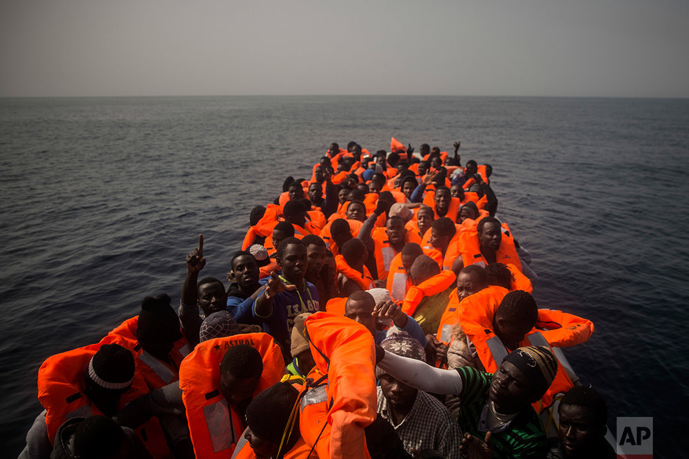 African refugees and migrants, mostly from Sudan and Senegal, wait aboard a rubber boat out of control to be assisted by an NGO, 25 miles north of Sabratha, off the Libyan coast, early in the morning on Thursday, Feb. 23, 2017. (AP Photo/Santi Palacios)