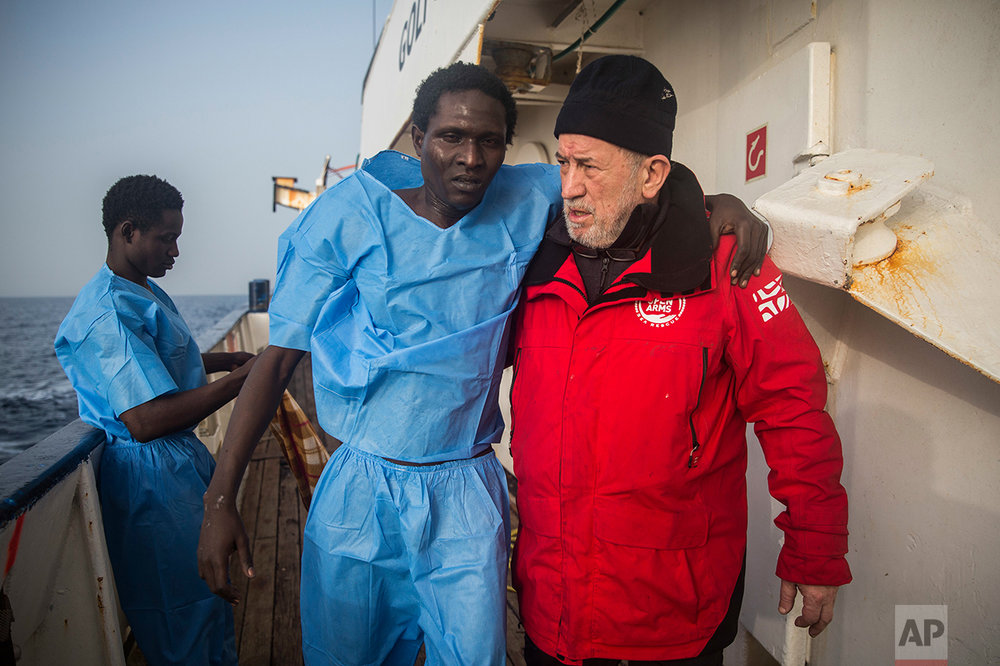 A member of the Spanish NGO Proactiva Open Arms crew helps an injured migrant aboard Golfo Azurro rescue ship, after a rescue operation 25 milles north of Sabratha, off the Libyan coast, early in the morning on Thursday Feb. 23, 2017. (AP Photo/Santi Palacios)