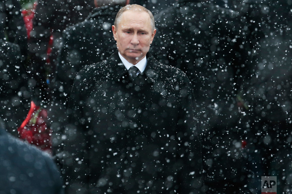 Snow falls as Russian President Vladimir Putin attends a wreath-laying ceremony at the Tomb of the Unknown Soldier in Moscow, Russia, Thursday, Feb. 23, 2017. The Defenders of the Fatherland Day, celebrated in Russia on Feb. 23, honors the nation's military and is a nationwide holiday. (AP Photo/Ivan Sekretarev)