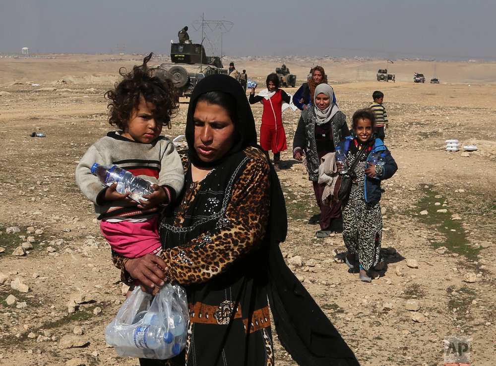 Displaced Iraqis flee their homes due to fighting between Iraqi special forces and Islamic State militants, on the western side of Mosul, Iraq, Thursday, Feb. 2017. The Iraqi security forces advance comes as part of a major assault that started five days earlier to drive Islamic State militants from the western half of Mosul, Iraq's second-largest city. (AP Photo/ Khalid Mohammed)