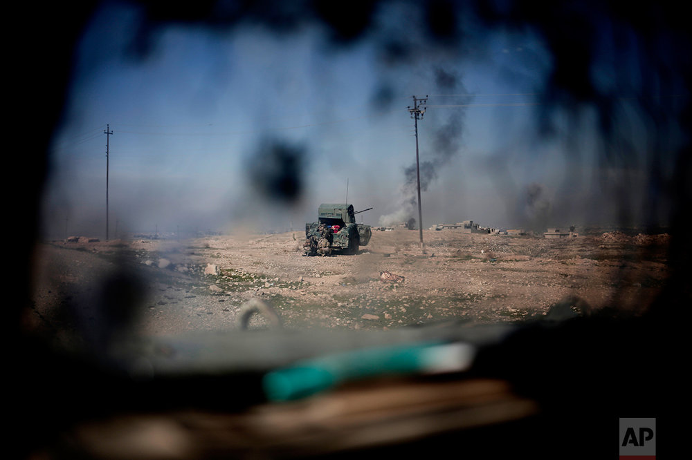 Iraqi police forces fire from a humvee at Islamic State positions from a hill side outside the town of Abu Saif, Monday, Feb. 20, 2017. (AP Photo/Bram Janssen)