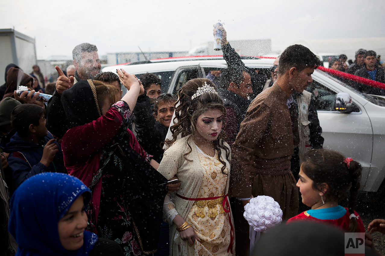 Hussein Zeino Danoon and Shahad Ahmed Abed arrive at the Khazer camp for people displaced from Mosul for their wedding on Thursday, Feb. 16, 2017. It's the second marriage to take place in the IDP camps east of the city where tens of thousands are living, having fled the fighting in Mosul. (AP Photo/Bram Janssen)